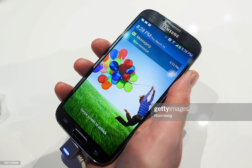 A Samsung Electronics Co. Galaxy S4 smartphone is held for a photograph during the Galaxy S4's release in Times Square in New York, U.S., on Thursday, March 14, 2013. Samsung Electronics Co. unveiled the Galaxy S4 with a bigger screen and software that tracks eye movements as the world's biggest smartphone seller takes its battle with Apple Inc. to the iPhone maker's home market. Photographer: Michael Nagle/Bloomberg via Getty Images
