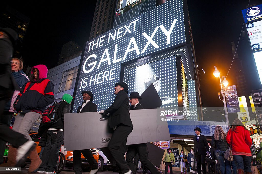 Samsung Electronics Co. signage is displayed on billboards as pedestrians walk by during the release of the Samsung Electronics Co. Galaxy S4 smartphone in Times Square in New York, U.S., on Thursday, March 14, 2013. Samsung Electronics Co. unveiled the Galaxy S4 with a bigger screen and software that tracks eye movements as the world's biggest smartphone seller takes its battle with Apple Inc. to the iPhone maker's home market. Photographer: Michael Nagle/Bloomberg via Getty Images