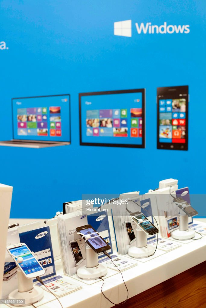 Samsung Electronics Co. smartphones sit on display beneath an advertisement for Windows-operated products inside a new Mobile TeleSystems (MTS) store in Moscow, Russia, on Tuesday, Nov. 6, 2012. OAO Mobile TeleSystems will extend cooperation with Microsoft Corp. and plans to sell Windows devices in its 5,000 Russian stores. Photographer: Alexander Zemlianichenko Jr./Bloomberg via Getty Images