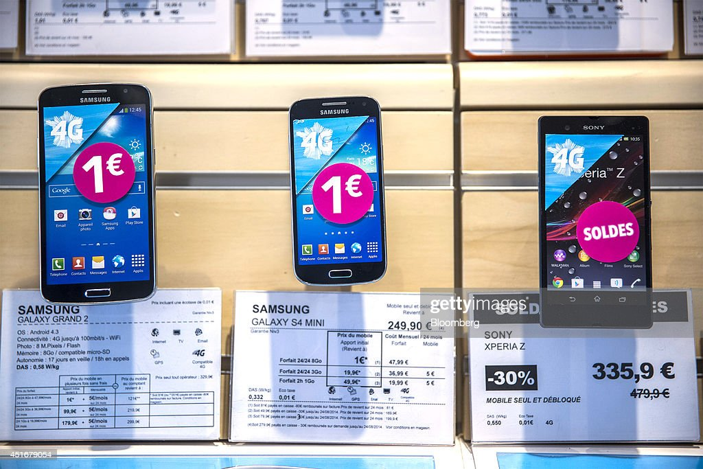 A Samsung Galaxy Grand 2, left, a Samsung Galaxy S4 Mini, center, smartphones manufactured by Samsung Electronics Co., sit alongside a Sony Xperia Z2 smartphone, manufactured by Sony Corp, are displayed for sale inside a Bouygues Telecom store, operated by Bouygues SA in Paris, France, on Thursday, July 3, 2014. Bouygues Telecom, France's third-largest mobile operator, was looking for a buyer as profitability and cash generation declined. Photographer: Balint Porneczi/Bloomberg via Getty Images