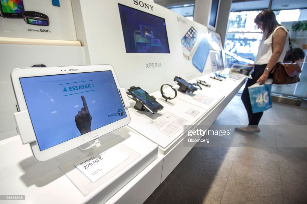 A Samsung Galaxy Tab 3 tablet device, manufactured by Samsung Electronics Co., sits on sale as customers browse products inside a Bouygues Telecom store, operated by Bouygues SA in Paris, France, on Thursday, July 3, 2014. Bouygues Telecom, France's third-largest mobile operator, was looking for a buyer as profitability and cash generation declined. Photographer: Balint Porneczi/Bloomberg via Getty Images
