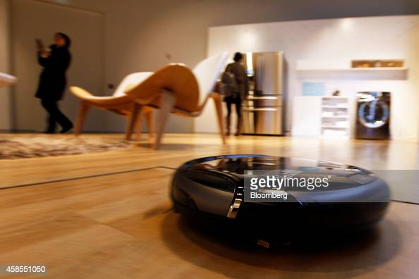 A Samsung NaviBot robot vacuum cleaner controlled through the Samsung Smart Home system moves through a product gallery at the Samsung Innovation...