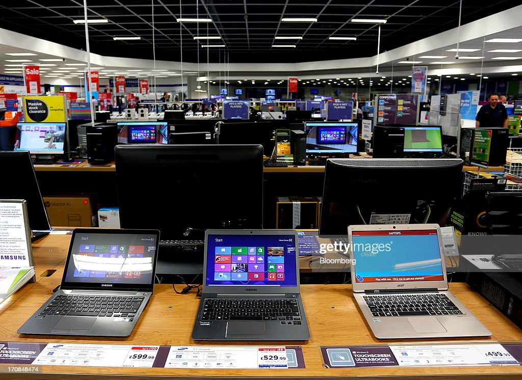 A Samsung Touchscreen Ultrabook, left, and a Samsung Ultrabook, center, manufactured by Samsung Electronics Co Ltd., sit alongside an Acer Inc. Ultrabook laptop computer inside a Currys and PC World 2 in 1 store, operated by Dixons Retail Plc, in Manchester, U.K., on Tuesday, June 18, 2013. Dixons Retail Plc, the U.K.'s largest consumer-electronics retailer, said last month it will report annual pretax profit at the 'top end' of analysts' predictions after fourth-quarter revenue beat estimates on increased sales of tablets and services such as software tutorials. Photographer: Paul Thomas/Bloomberg via Getty Images