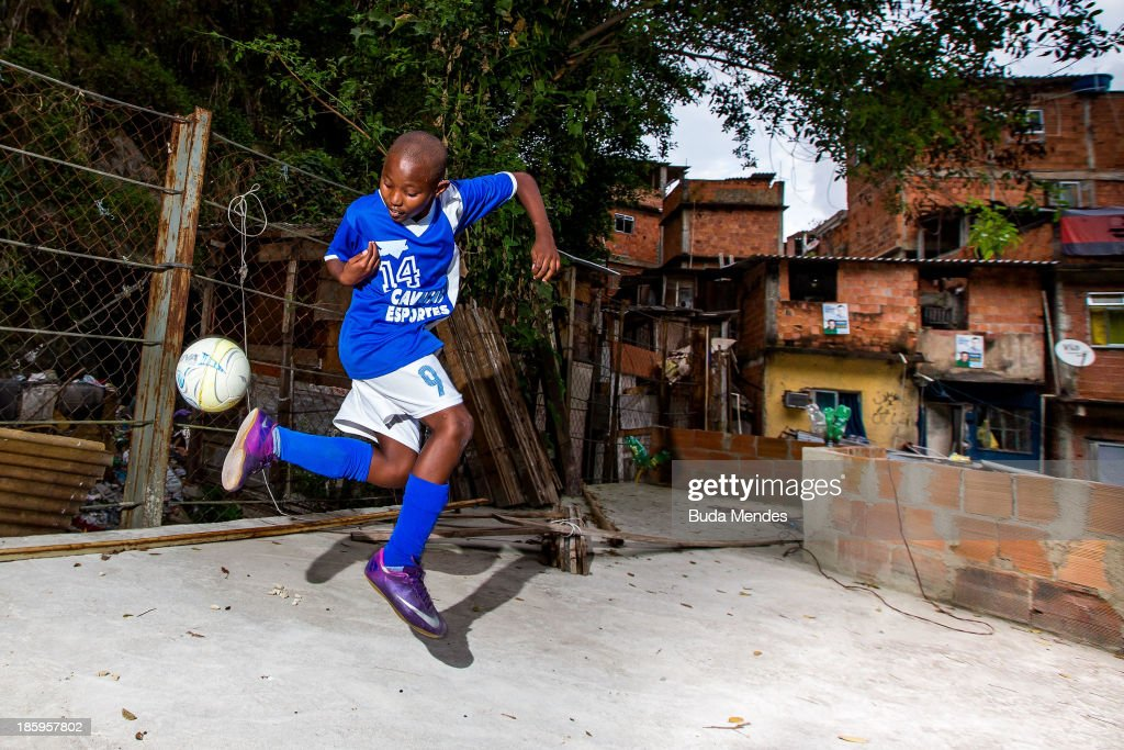 Samuca, athlete of Vila Nova Project, plays football on the rooftops in the Morro dos Macacos area on October 26, 2013 in Rio de Janeiro, Brazil. The Project Vila Nova was idealized by Alex Sandro and has so far run for 2 years, catering to children and young residents of the Morro dos Macacos area.