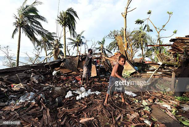 Samuel and his father Phillip search through the ruins of their family home on March 16 2015 in Port Vila Vanuatu Cyclone Pam has hit South Pacific...