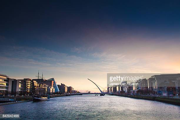 Samuel Beckett Bridge Over River Amidst Buildings At Dusk