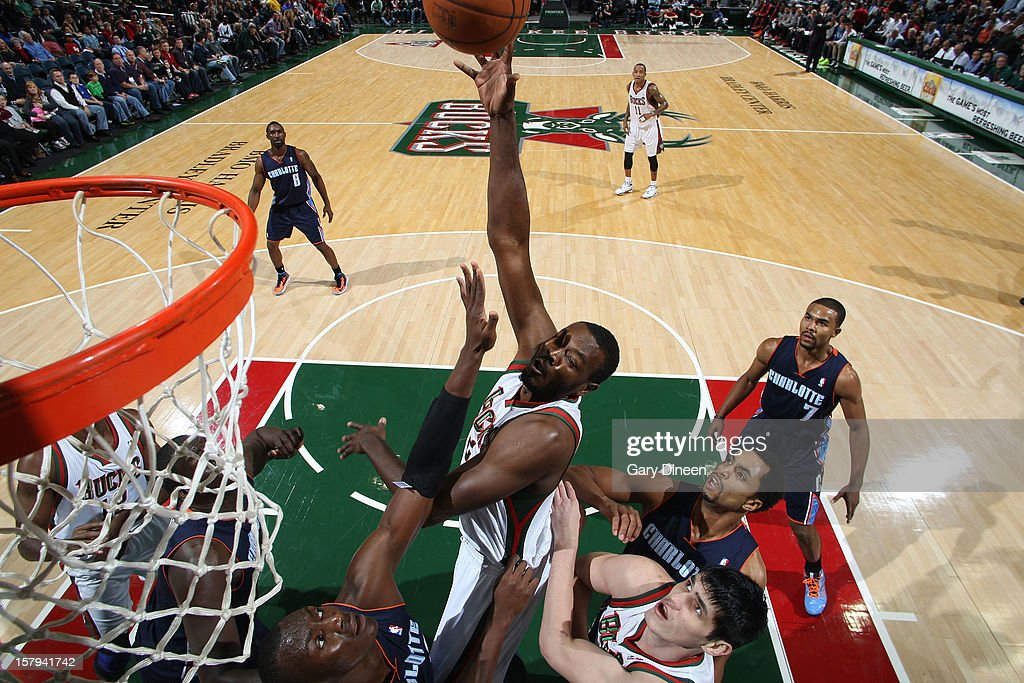 Samuel Dalembert #21 of the Milwaukee Bucks shoots against (L-R) Bismack Biyombo #0 and Gerald Henderson #9 of the Charlotte Bobcats during the game on December 7, 2012 at the BMO Harris Bradley Center in Milwaukee, Wisconsin.