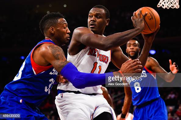 Samuel Dalembert of the New York Knicks looks to pass around Robert Covington of the Philadelphia 76ers in the second half at Madison Square Garden...