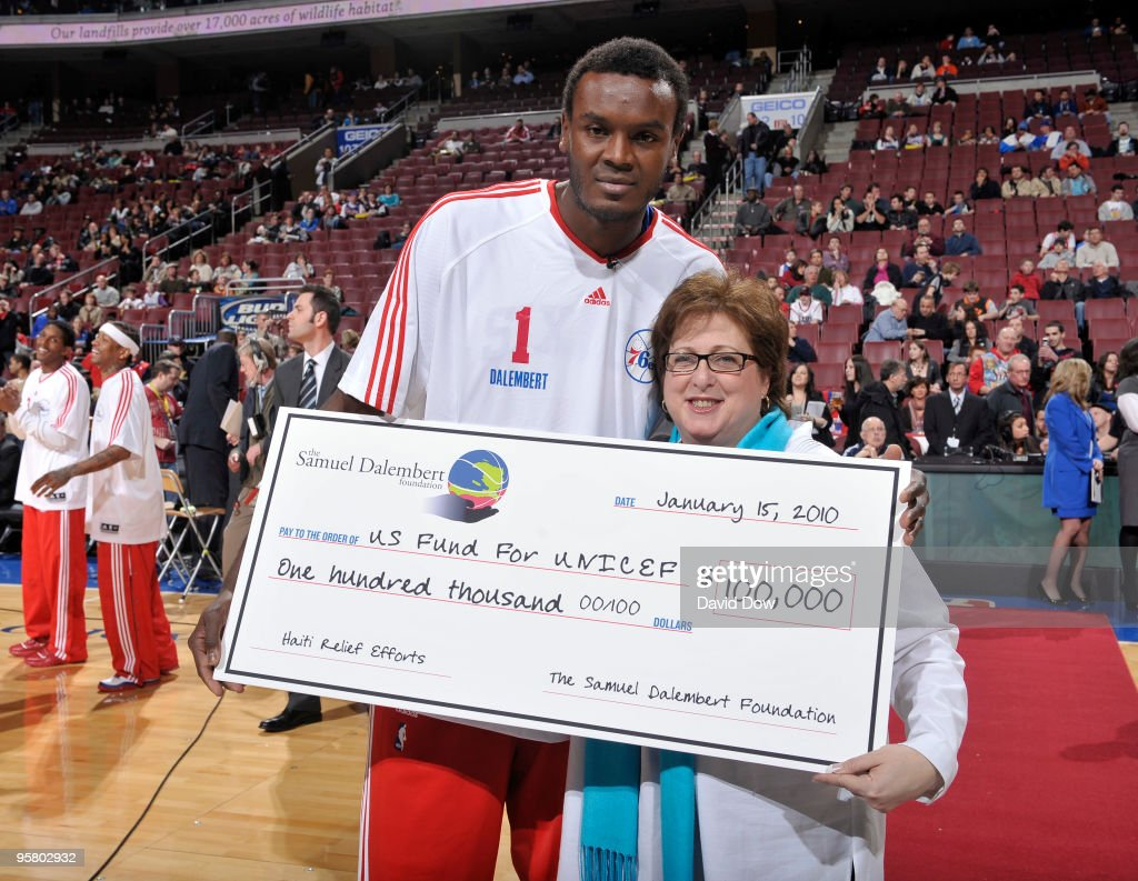 Samuel Dalembert of the Philadelphia 76ers presents Caryl Stern of UNICEF a $100000 check before the basketball game against the Sacramento Kings on...