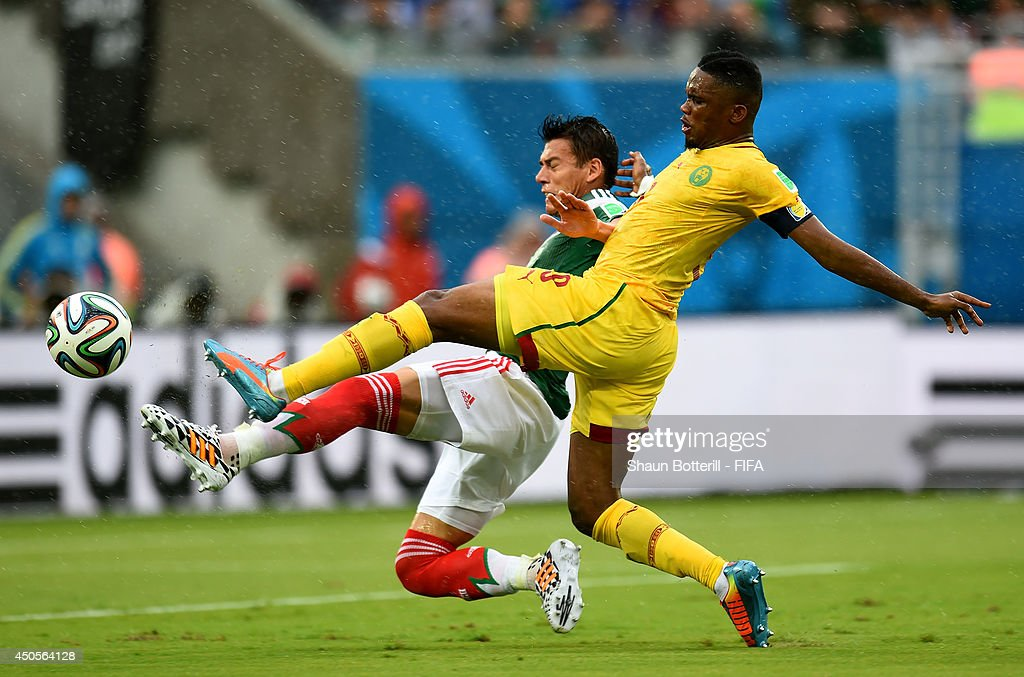 Samuel Eto'o of Cameroon is challenged by Hector Moreno of Mexico during the 2014 FIFA World Cup Brazil Group A match between Mexico and Cameroon at...