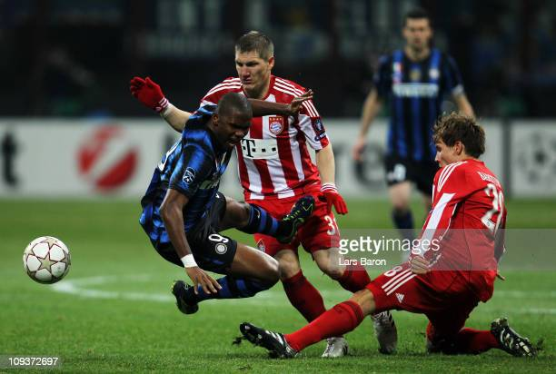 Samuel Eto'o of Inter is challenged by Bastian Schweinsteiger and Holger Badstuber of Muenchen during the UEFA Champions League round of 16 first leg...