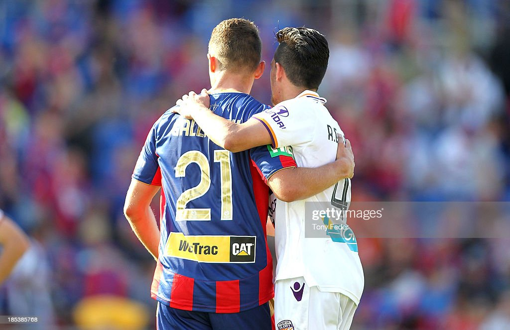 Samuel Gallaway of the Jets and Ryan Edwards of the Glory embrace after drawing nil all during the round two A-League match between the Newcastle Jets and the Perth Glory at Hunter Stadium on October 20, 2013 in Newcastle, Australia.