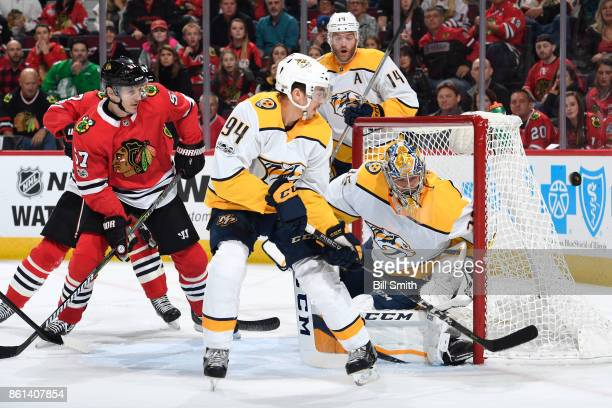 Samuel Girard of the Nashville Predators and Tommy Wingels of the Chicago Blackhawks watch the puck fly by goalie Pekka Rinne in the first period at...