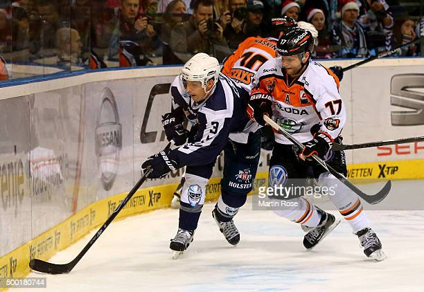 Samuel Klassen of Hamburg Freezers battles for the puck with Sbastian Furchner of Grizzly Wolfsburg during the DEL game between Hamburg Freezers and...