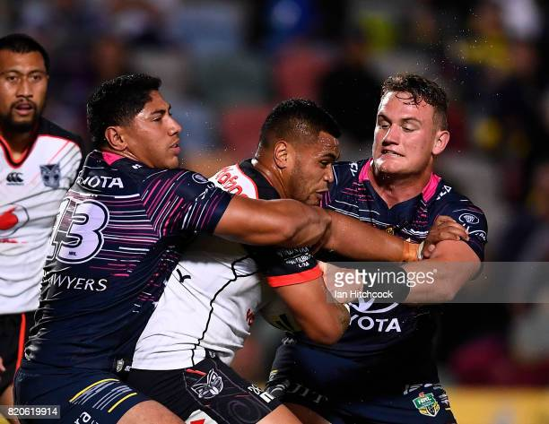 Samuel Lisone of the Warriors is tackled by Jason Taumalolo and Coen Hess of the Cowboys during the round 20 NRL match between the North Queensland...