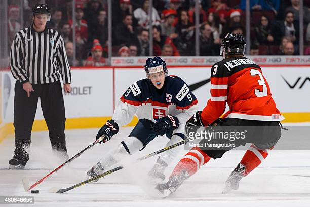 Samuel Petras of Team Slovakia tries to get the puck past Dillon Heatherington of Team Canada during the 2015 IIHF World Junior Hockey Championship...