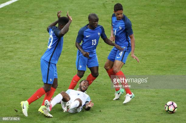 Samuel Umtiti N'golo Knate and Raphael Varane of France slash Raheem Sterling of England during the International Friendly match between France and...