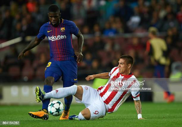 Samuel Umtiti of Barcelona is tackled by Uros Djurdjevic of Olympiakos during the UEFA Champions League group D match between FC Barcelona and...