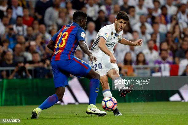 Samuel Umtiti of FC Barcelona and Marco Asensio of Real Madrid battle for the ball during the La Liga match between Real Madrid CF and FC Barcelona...