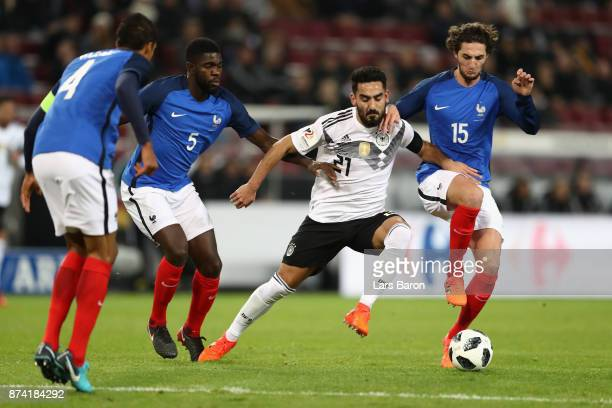 Samuel Umtiti of France and Adrien Rabiot of France battle for possession with IIkay Gundogan of Germany during the international friendly match...