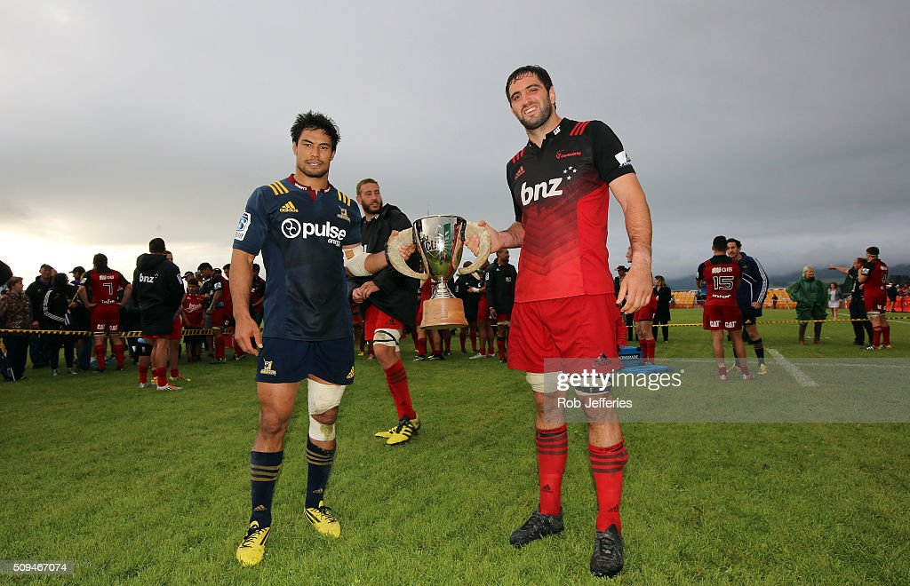 Samuel Whitelock of the Crusaders and Shane Christie of the Highlanders pose for a photo with the Farmlands Cup after a 19 all draw during the Super Rugby trial match between the Highlanders and the Crusaders at Fred Booth Park on February 11, 2016 in Waimumu, New Zealand.