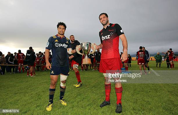 Samuel Whitelock of the Crusaders and Shane Christie of the Highlanders pose for a photo with the Farmlands Cup after a 19 all draw during the Super...