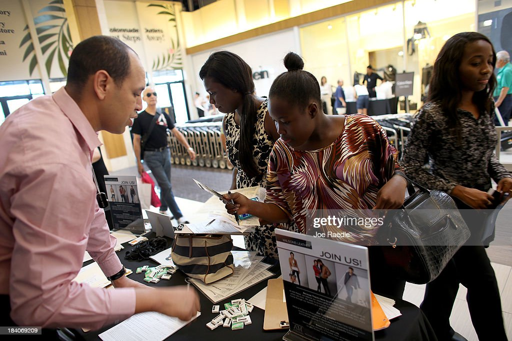 Samuella Augustin, Rodacheca Nelson and Lise Andre (L-R) speak with Ahmed Nifa about the jobs available at Wilsons Leather Outlet during a job fair at Sawgrass Mills on October 11, 2013 in Sunrise, Florida. As the holiday season approaches many of the roughly 50 retailers at the job fair including Banana Republic, J.Crew Factory, Victoria's Secret and Calvin Klein are starting to hire people for seasonal work as well as continuing to look for qualified full time employees.