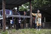 A samurai horseman stands next to horses in a barn during the Soma Nomaoi festival in Minamisoma Fukushima Prefecture Japan on Sunday July 24 2016...