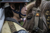 A samurai horseman tends to a horse while waiting for a procession to start during the Soma Nomaoi festival at the Nakamura Shrine in Soma Fukushima...
