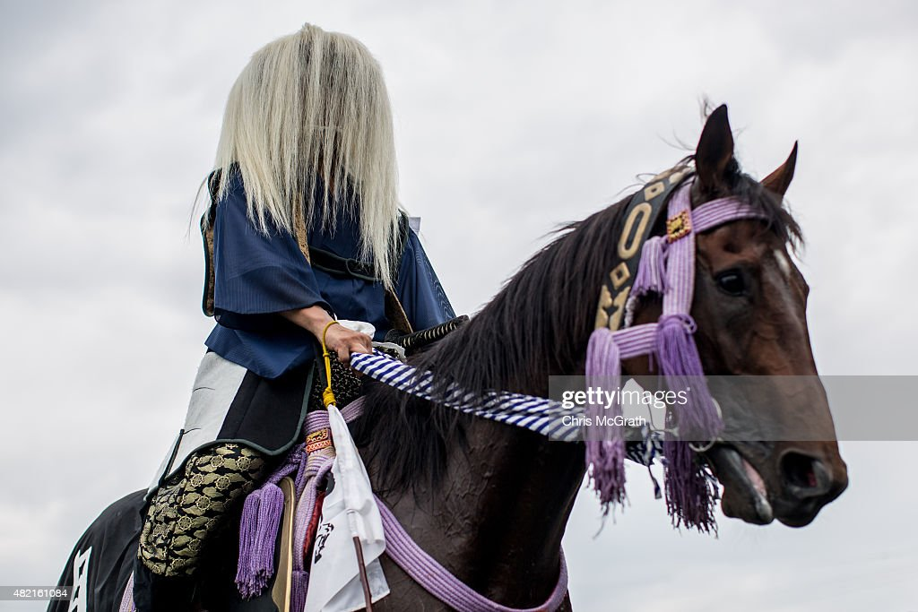 A Samurai horseman waits for a parade to start after the morning ritual at Ohta Shrine ahead of the the Soma Nomaoi festival on July 25, 2015 in Minamisoma, Japan. Every summer the people of Fukushima prefecture have gathered to honor the ancient traditions of the Samurai at the Soma Nomaoi festival. The festival started as a military exercise more than 1000 years ago by Taira no Kojiro Masakado the founder of the Soma Clan. The three-day Shinto festival sees more than 500 horsemen recreate ancient battle scenes from the Edo Period (1603-1869). Soma city, Minamisoma and the surrounding towns of Fukushima prefecture, famous for their samurai and horse breeding traditions were heavily affected by the 2011 Tohoku earthquake and Tsunami and the following nuclear accident at the Fukushima Daiichi Nuclear Plant. Minamisoma sits just 25 kilometers north of the nuclear power plant and residents were forced to evacuate as much of the city fell in the radiation exclusion zone. In April 2012, residents of Minamisoma were able to return to their homes after the exclusion zone was moved to 10 kilometers. The tradition of the Soma Nomaoi is extremely important to the local community, and despite the ongoing clean up operations and many of the participants losing their homes, horses and belongings, including their armor, weapons and ceremonial clothing, the festival has never been cancelled, although some events were postponed in 2011 the festival was held at full scale again in 2012 and since then has gained in momentum with local residents keen to pass on the traditions to younger generations.