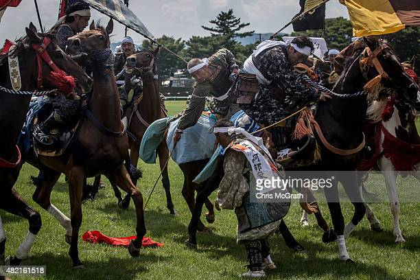 Samurai horsemen fight for a flag during the Shinkisoudatsusen at the Soma Nomaoi festival at Hibarigahara field on July 26 2015 in Minamisoma Japan...