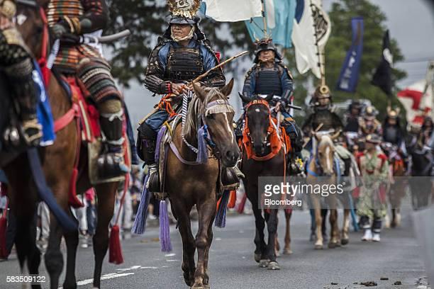 Samurai horsemen make their way through a street during the Soma Nomaoi festival in Minamisoma Fukushima Prefecture Japan on Sunday July 24 2016...