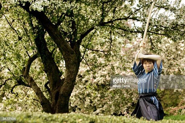 Samurai performer Miho Tsuji demonstrates a manuever beneath cherry trees during a press preview for Brooklyn Botanic Garden's Annual Sakura Matsuri...