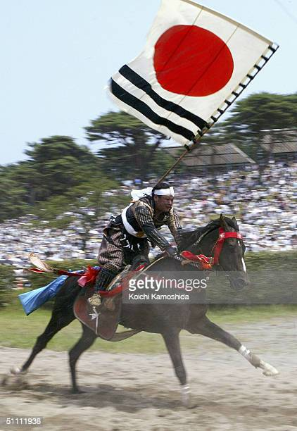 Samurai Riders dressed in full medieval armour take part in an equestrian contest during the SomaNomaoi festival on July 24 2004 in Haramachi City...