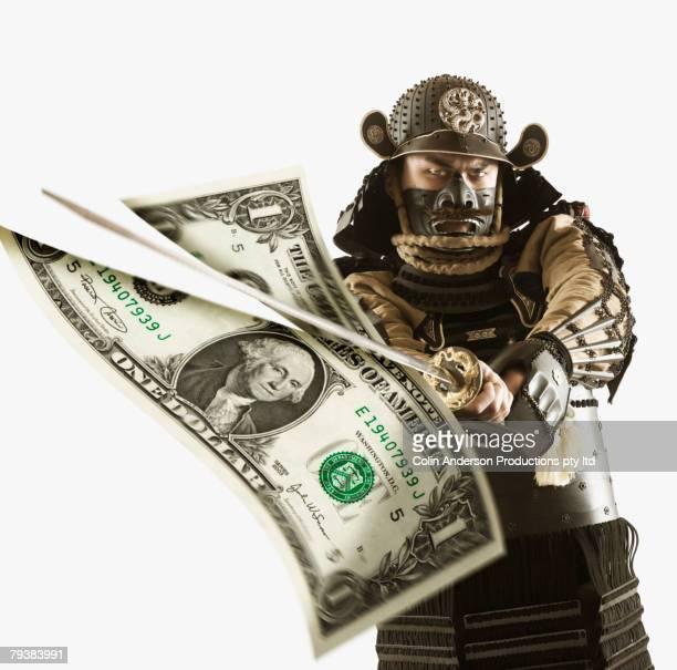 Samurai slicing dollar bill with sword