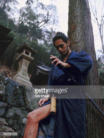 Samurai warrior leaning against a tree : Stock Photo