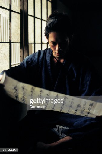 Samurai warrior reading a Japanese document : Stock Photo