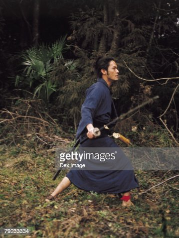 Samurai warrior walking with a sword in his hand : Stock Photo