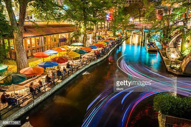 Riverwalk de San Antonio, Texas, con vista al canal del turismo sombrillas por la noche