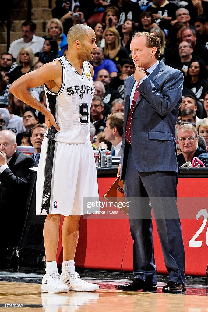 San Antonio Spurs assistant coach Mike Budenholzer speaks with Tony Parker #9 as the team plays the Miami Heat during Game Three of the 2013 NBA Finals on June 11, 2013 at AT&T Center in San Antonio, Texas.