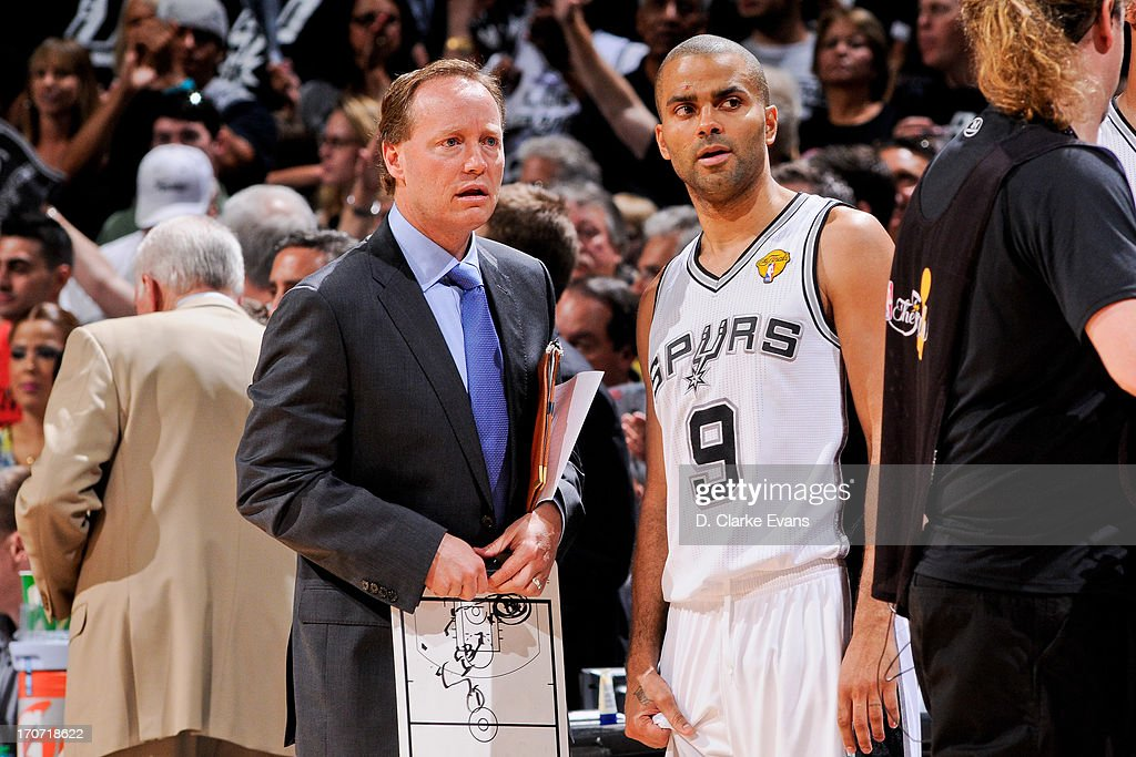 San Antonio Spurs assistant coach Mike Budenholzer speaks with Tony Parker #9 while playing the Miami Heat during Game Five of the 2013 NBA Finals on June 16, 2013 at AT&T Center in San Antonio, Texas.