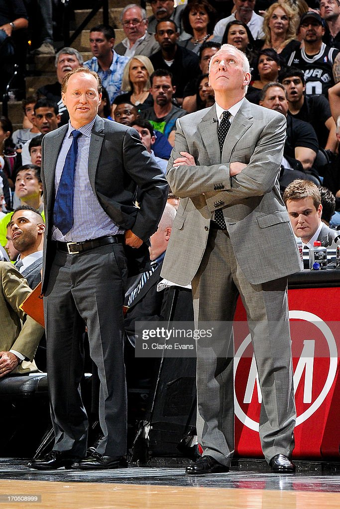 San Antonio Spurs Head Coach Gregg Popovich and assistant coach Mike Budenholzer look on as the team plays the Miami Heat during Game Four of the 2013 NBA Finals on June 13, 2013 at AT&T Center in San Antonio, Texas.