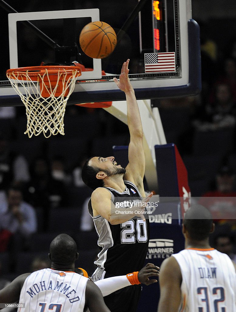 San Antonio Spurs' Manu Ginobili (20) does a reverse layup past Charlotte Bobcats' Nazr Mohammed (13) and Boris Diaw (32) during the first half at Time Warner Cable Arena in Charlotte, North Carolina, Monday, November 8, 2010.