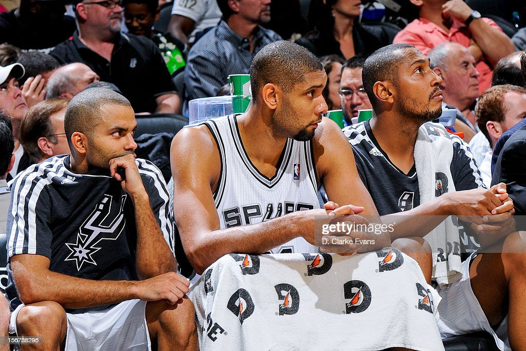 San Antonio Spurs players, from left, Tony Parker #9, Tim Duncan #21 and Boris Diaw #33 look on from the bench as their teammates play the Los Angeles Clippers on November 19, 2012 at the AT&T Center in San Antonio, Texas.