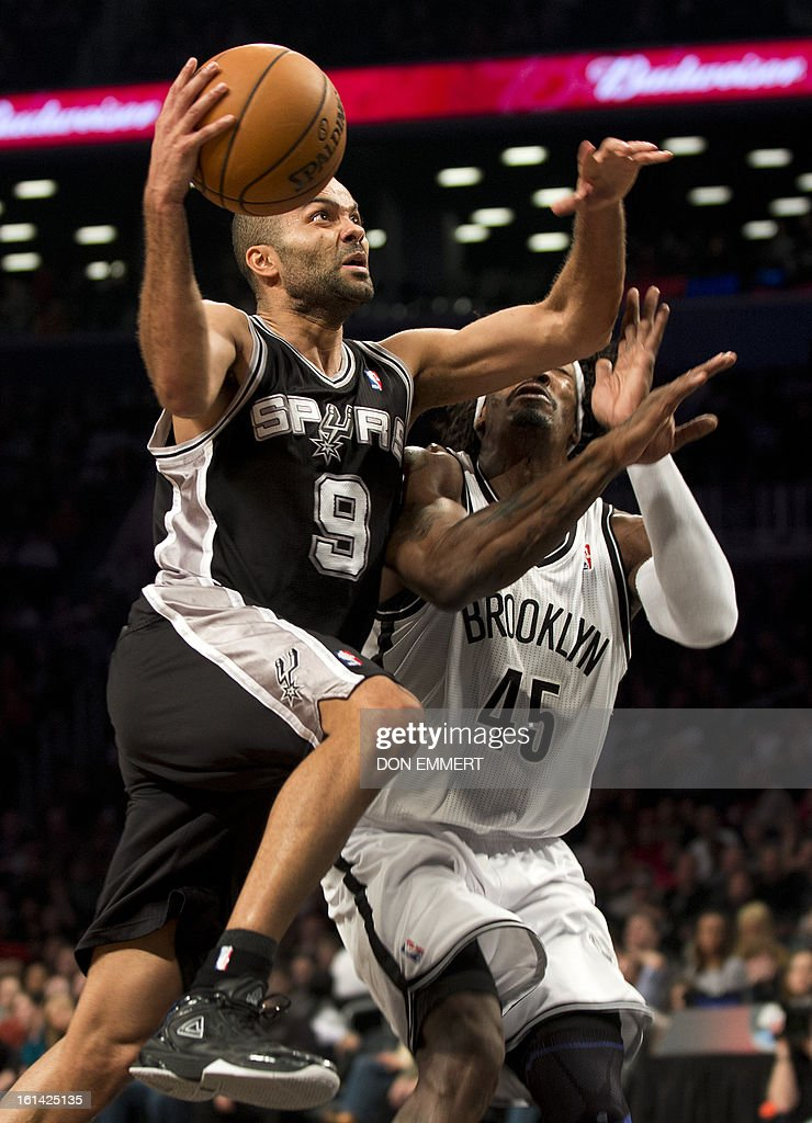 San Antonio Spurs Tony Parker (L) drives to the hoop past Brooklyn Nets Gerald Wallace during their NBA game February 10, 2013 at the Barclay Center in New York.