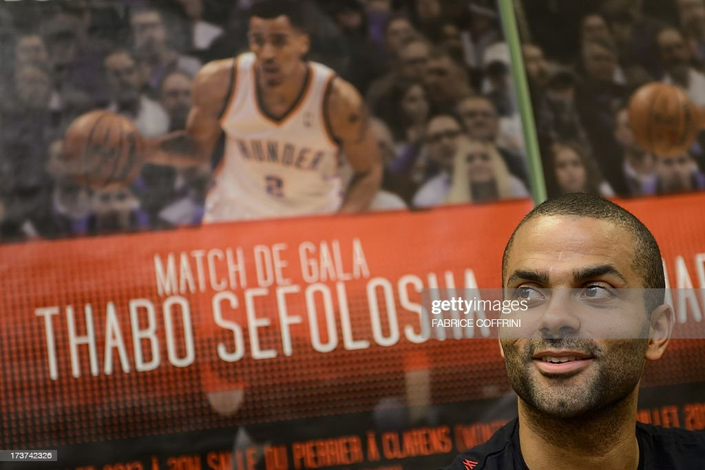 San Antonio Spurs' Tony Parker of France reacts to a picture of Oklaoma City Thunder's Thabo Sefolosha of Switzerland during a press conference ahead of a charity basketball match on July 17, 2013 in Clarens near Montreux, western Switzerland.