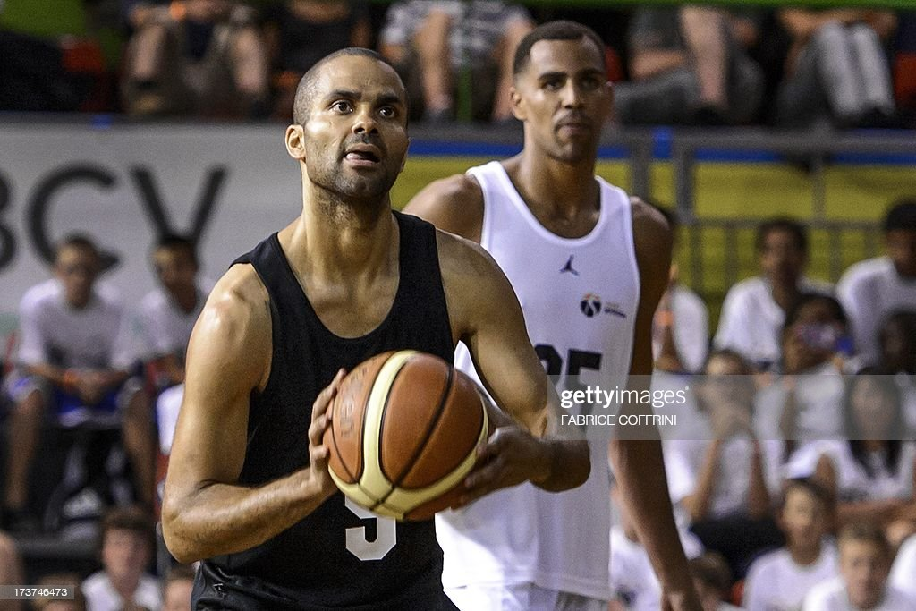 San Antonio Spurs' Tony Parker of France (L) shoots next to Oklahoma City Thunder's Thabo Sefolosha of Switzerland during a charity basketball match organised by Sefolosha on July 17, 2013 in Clarens near Montreux, western Switzerland.