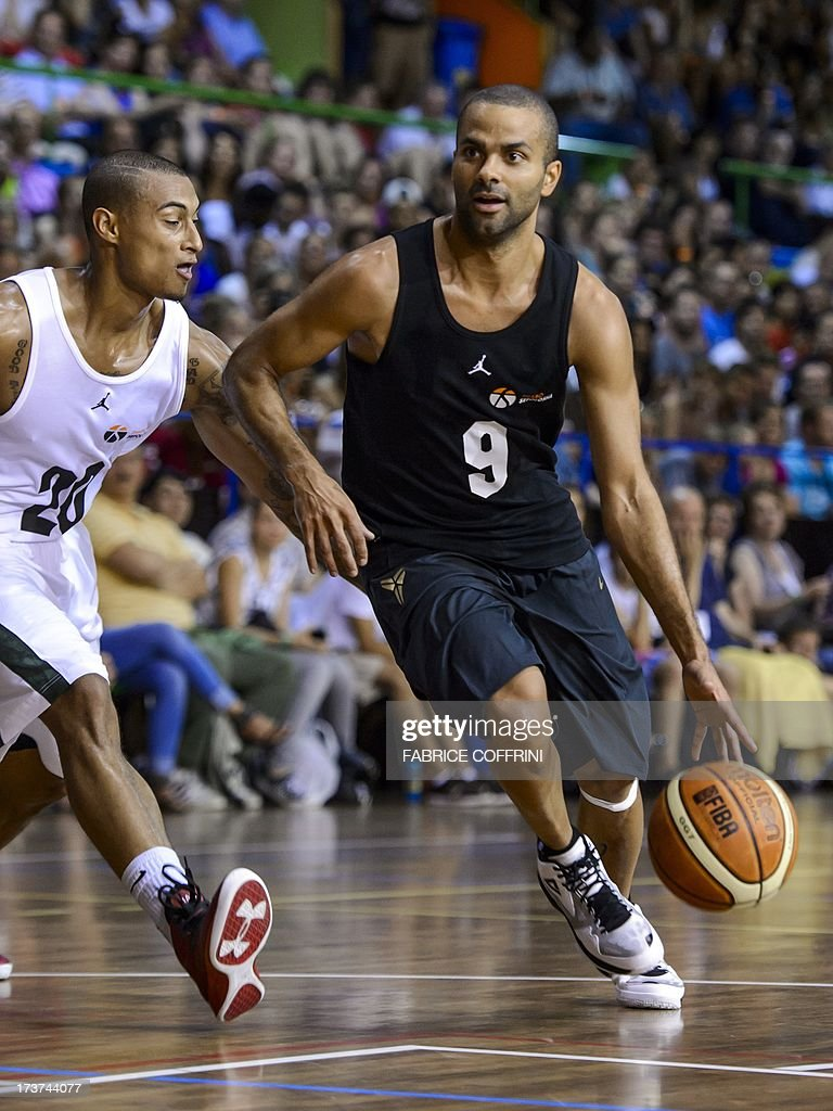 San Antonio Spurs' Tony Parker of France (R) vies with ASVEL's Edwin Jackson during a charity basketball match organised by Oklaoma City Thunder's Swiss player Thabo Sefolosha on July 17, 2013 in Clarens, western Switzerland.