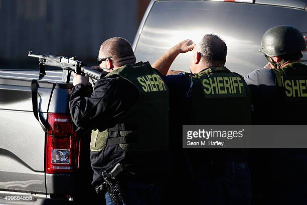 San Bernadino Sheriff officers point weapons into a neighborhood as they pursue suspects of the shooting at the Inland Regional Center on December 2...