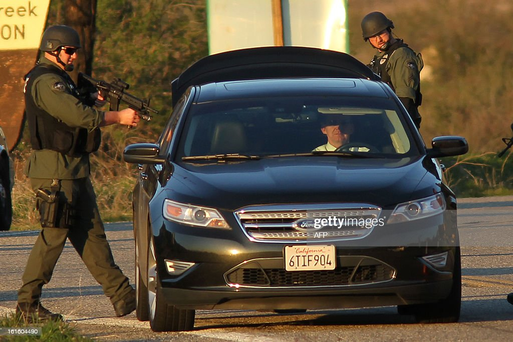 San Bernardino County sheriff's deputies search a vehicle on Highway 38, leaving the Big Bear Lake area, as a standoff with the ex Los Angeles police officer believed to now be a quadruple murder suspect Christopher Dorner continues with the cabin he is believed to be in burning, near San Bernardino, California, on February 12, 2013, some 46 miles (75 km) from the San Bernardino Mountains near Big Bear where Dorner, a former Los Angeles, has barricaded himself in a cabin and exchanged gunfire with police who have the cabin surrounded. AFP PHOTO / David McNew